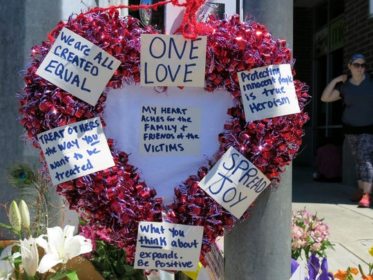 A heart-shaped wreath covered with positive messages hangs on a traffic light pole at a memorial for two bystanders who were stabbed to death Friday.