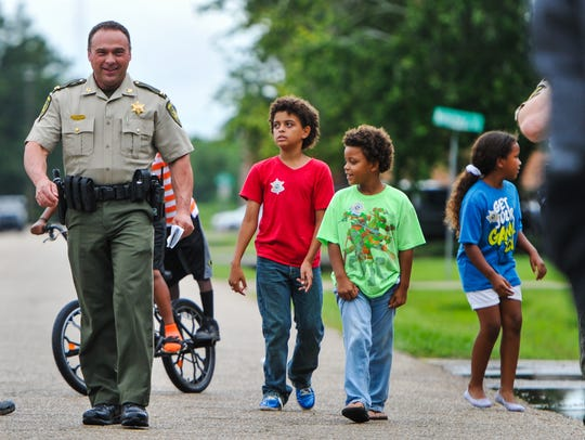 Carlos Stutes with the Lafayette Parish Sheriff's Office visits with children while he and other deputies walking neighborhoods in the parish June 12, 2017.