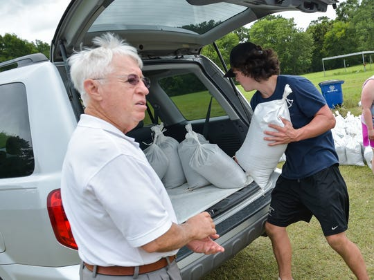 Josh Wimmer helps load sand bags for Walter Martin in Youngsville.  Wednesday, June 21, 2017.