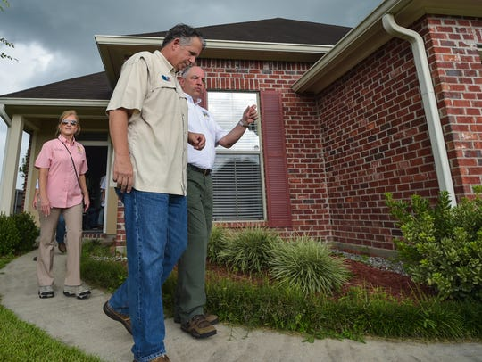 Gov. John Bel Edwards and First Lady Donna Edwards are shown with Lafayette Mayor-President Joel Robideaux visiting Youngsville homes damaged in the August 2016 floods on the one-year anniversary of the floods.
