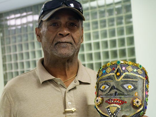 "Alton ""lil tiger"" Armstrong holding traditional mask"
