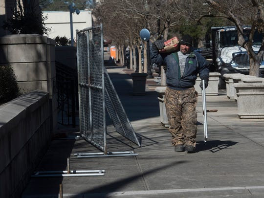 Jon Stetz with the Hagen Fence Co. puts up a temporary fence on Wednesday, Jan. 17, 2018, around the U.S. District Courthouse at 1 N. Palafox St. in downtown Pensacola.