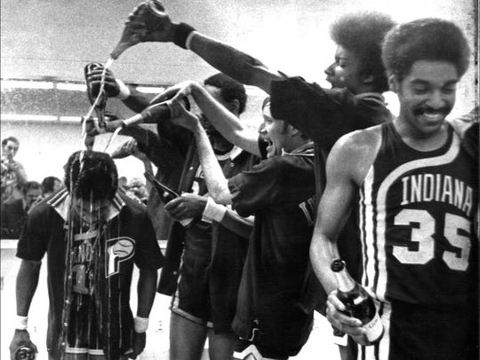 Pacers players doused teammate John Barnhill with champagne after they won the ABA championship on May 20, 1972, defeating the New York Nets 108-105. At right is Pacer Roger Brown, who starred in the game.