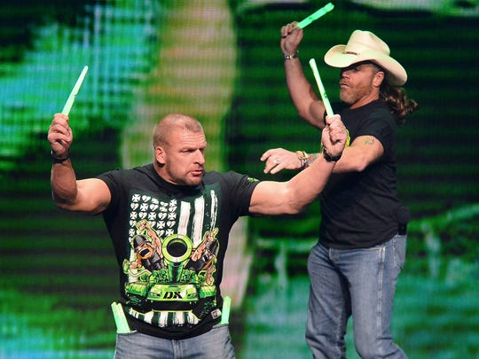 WWE personalities Triple H (L) and Shawn Michaels throw glow sticks into the crowd at a news conference announcing the WWE Network at the 2014 International CES at the Encore Theater at Wynn Las Vegas on January 8, 2014 in Las Vegas.