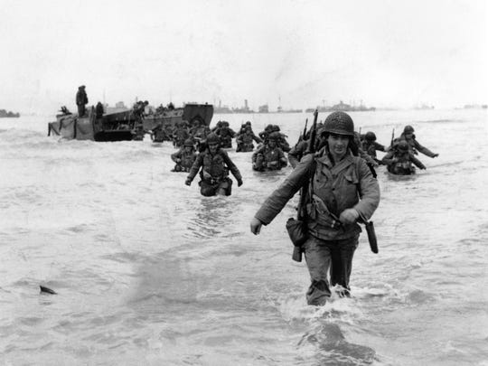 U.S. infantrymen wade through the surf as they land at Normandy in the days following the Allies' June 1944, D-Day invasion of occupied France. An allied ship loaded with supplies and reinforcements waits on the horizon.  (AP Photo/Bert Brandt) [Via MerlinFTP Drop]