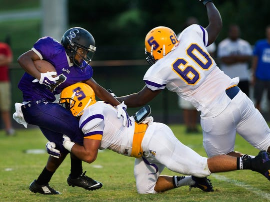 Smyrna's Austin Brown (8) forces Cane Ridge's Brysen Terrell (4) backward for a loss of yardage Friday, August 29, 2014 at Cane Ridge High School in Antioch, Tenn.