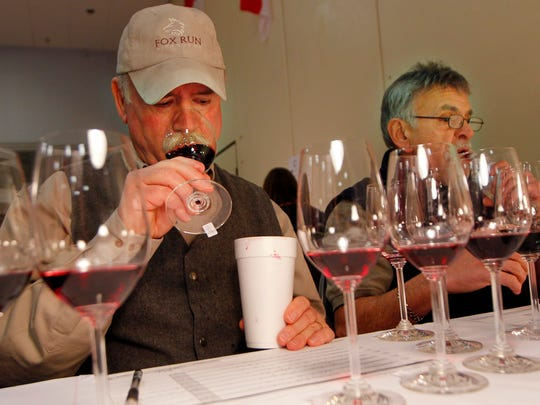 Scott Osborn, owner of Fox Run Vineyards in Penn Yan, left, and Tony DiChario of Pittsford judge a flight of reds during the 14th annual Finger Lakes International Wine Competition at the Rochester Plaza in Rochester Sunday afternoon, March 30, 2014.