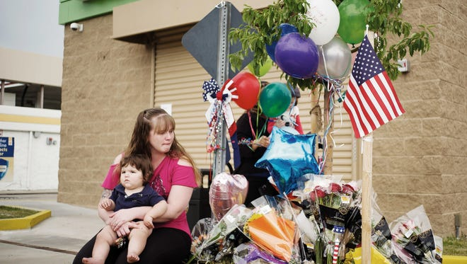 In this Monday, June 20, 2016, photograph, Samantha Mason cradles her 1-year-old child, Julian, near a memorial outside a marijuana dispensary in Aurora, Colo., in which her husband, 24-year-old Travis Mason, was shot and killed while working as a security guard last weekend. The slaying was the first known on-the-job death at a licensed marijuana business in Colorado.