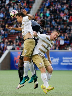 FC Cincinnati forward Djiby Fall (9), center, goes up for a challenge against Louisville City FC defender Paco Craig (18), left, in the first half.