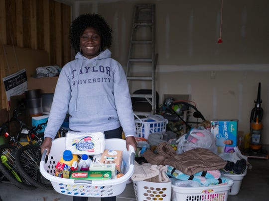 Winnie Bulaya, Camby, holds a load of donated goods