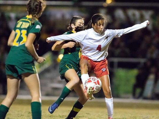 Centennial High School Hawk Jennifer Enriquez defends the ball against Mayfield Trojan Kaitlyn Cosgrove during girls prep soccer playoff game on Friday.