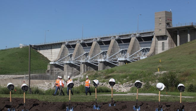 Ames Construction employees pass walk behind shovels for the ceremonial groundbreaking of the Red Rock Hydroelectric Project near Pella Wednesday, Aug. 13, 2014. The Red Rock Dam is seen in the background.