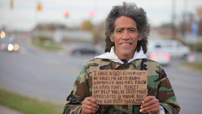 Ted Williams holds a sign advertising his smooth radio voice near a highway ramp in Columbus, Ohio, in 2010.