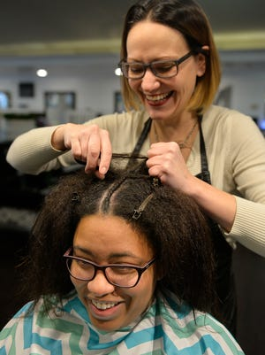 Monica Voth of Mantra Salon and Spa in St. Cloud works to braid reporter Vicki Ikeogu's hair Dec. 22 at the salon.