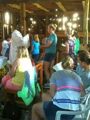 Father Eloo serves  communion to Sarah Gisler at an