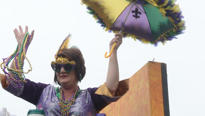 A Krewe of Fleur de Lis member waves to the crowd at the 2015 Krewe Parade in Alexandria.