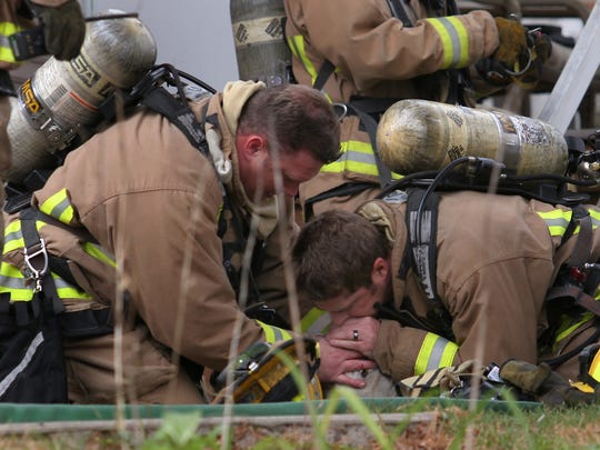Wausau firefighters give artificial respiration to a dog that was rescued in 2011 from a house fire.
