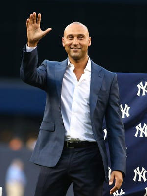New York Yankees legend Derek Jeter waves to the crowd during the ceremony retiring Bernie Williams' No. 51 prior to a game against the Texas Rangers at Yankee Stadium.