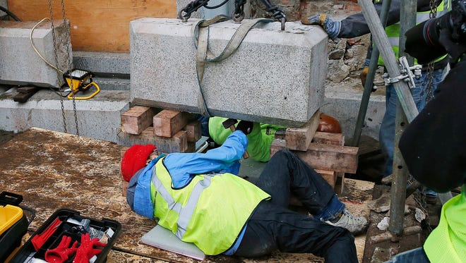 Massachusetts officials work to remove a time capsule in the cornerstone of the Statehouse in Boston, Thursday, Dec. 11, 2014.