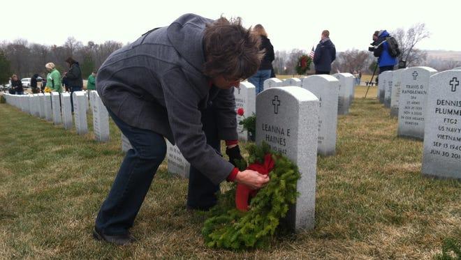 Volunteer Teresa Cochran of St. Charles places wreaths for National Wreaths Across America Day on Saturday in Van Meter.