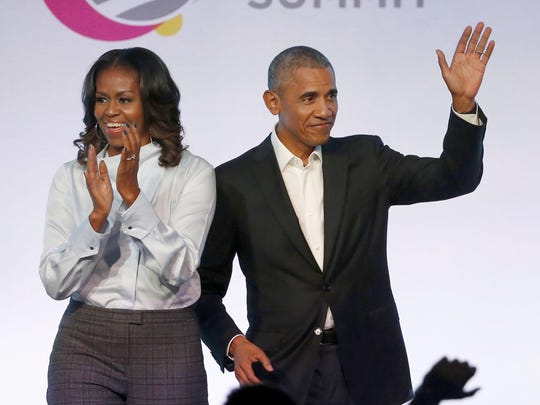 Former President Barack Obama and former first lady Michelle Obama appear at the Obama Foundation Summit in Chicago.