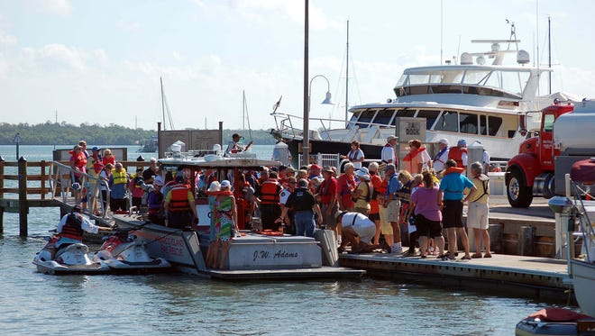 "File: ""Wear It"" participants gather on a dock at Rose Marina to express their solidarity with the international record-breaking attempt at wearing jackets together at one time."