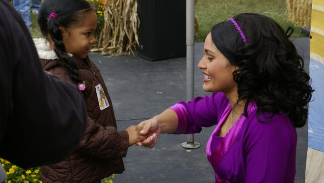 Jennifer Pena, as Miss Rosa, chats with a young PBS fan at an event.