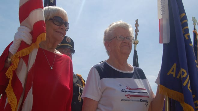 Flossie Wiesend, left, Kay Owens, right, hold flags during a Memorial Day event at Mountain Home Plaza.