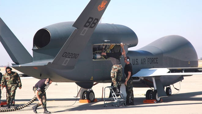 Avionics specialists with the 12th Aircraft Maintenance Unit prepare a Global Hawk for a runway taxi test at Beale Air Force Base, Calif. The Global Hawk is scheduled to begin flying at Beale in early November. The program is a total force effort with the Air Force Reserve's 13th Reconnaissance Squadron assisting active duty personnel.