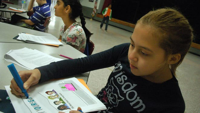 Sixth-grader Lily Alvarado colors her financial literacy book at Rucker-Stewart Middle School in Gallatin. Schoolmate Maitri Patel sits to the left.