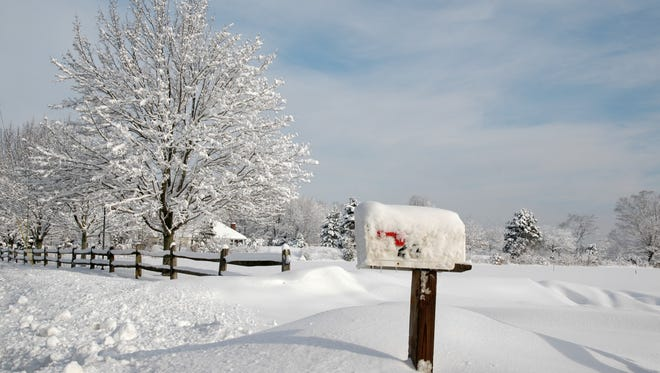 Snow-covered mailbox against a cold winter landscape