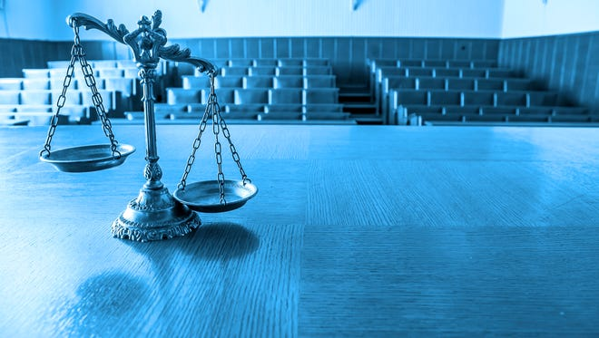 Scales of justice in empty courtroom.