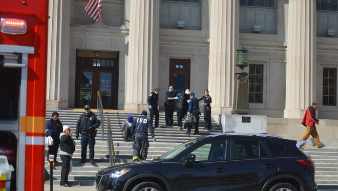 Firefighters treat people on the steps of the Indianapolis Central Library, 40 W. St. Clair St., on Saturday.