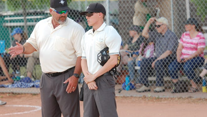 Veteran umpire Chris Walker, left, helps a younger umpire during a recreational baseball game Wednesday in Windsor.