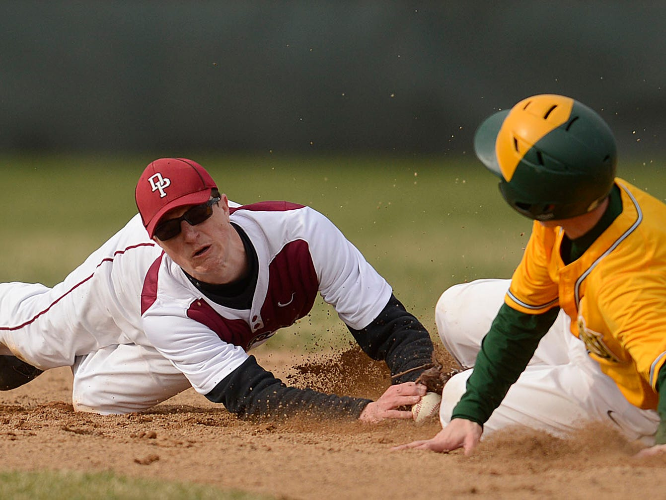 De Pere's Hunter Staniske (11) tries to tag out Ashwaubenon's Will Ark (23) during a play at second base in Tuesday's baseball game at Ashwaubomay Park in Ashwaubenon. Evan Siegle/Press-Gazette Media