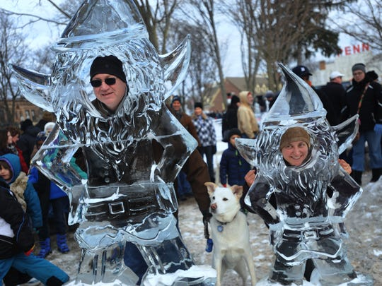 "Frank Forest, left, his wife Michela and their dog ""Chuy"" get their photo taken with an interactive ice carving of elves at the 33rd Annual Plymouth Ice Festival."