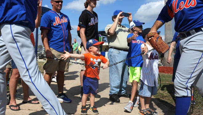 William Swiss 3 of Port St. Lucie looks for a hive five from some of the Met players as they switch practice fields. Behind him is his father William Swiss Jr. They were there with visiting grandparents William Swiss Sr. and his wife Sharon from Franklin Twp. in Sussex County, New Jersey.