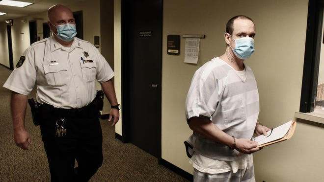 Monroe County Sheriff Office Deputy Matt Brodie escorts Kenny W. McBride, 45, who is facing charges of open murder and mutilation of a corpse.