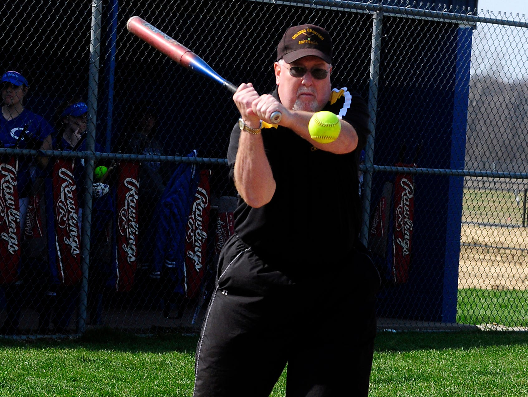 Colonel Crawford softball coach Chuck Huggins hits ground balls before a game. Huggins is a member of the state softball coaches hall of fame and is entering his 27th season with the Eagles.