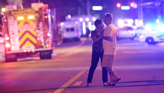 Family members wait for word from police after arriving down the street from a shooting involving multiple fatalities at Pulse Orlando nightclub in Orlando, Fla., Sunday, June 12, 2016.