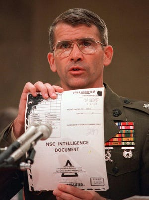 """Lt. Col. Oliver North holds up a National Security Council Intelligence Document marked """"TOP SECRET"""" during testimony  before the House-Senate investigating committee at the Iran-Contra hearings in Washington July 11, 1987."""
