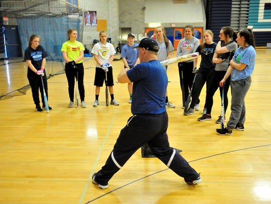 Great Falls High assistant softball coach Don Meirhoff demonstrates hitting technique during the Bison practice last Friday at Swarthout Fieldhouse.