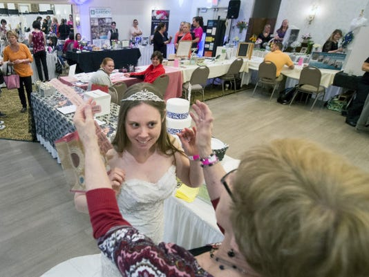 Lauren Nimal, center, has her tiara adjusted by her future mother-in-law Elaine Riegel during Brides Against Breast Cancer on Sunday in West Manchester Township.