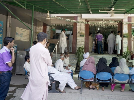 Pakistani applicants wait outside the office of Pakistan's National Data Registration Authority Aug. 24 to collect their identity cards in Islamabad, Pakistan.