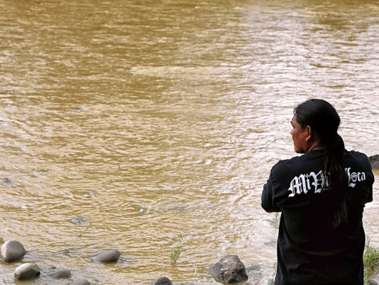 Travis Sells, of Farmington, stops to look at the sludge flowing through the Animas River from the Gold King Mine spill Aug. 8 at Berg Park in Farmington. More than a month later, state officials have announced that fish caught in portions of the Animas and San Juan rivers affected by the spill are safe to eat.