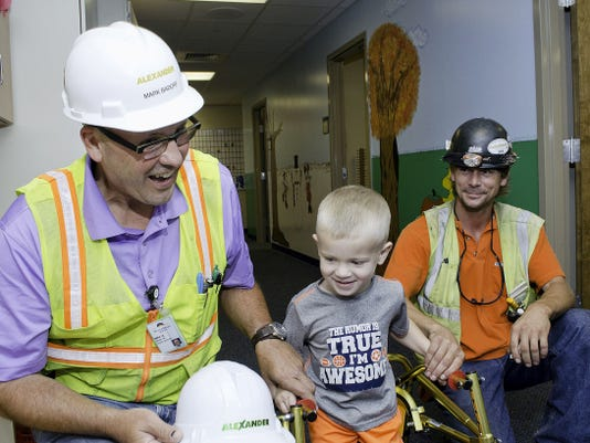 Alexander Building Construction's Mark Badorf, left, and Gettle Inc.'s Mike Ferree, right, take time to visit 3-year-old Owen Lewis during one of his physical and speech therapy sessions to present him with his very own hard hat at York Hospital.
