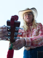 Bonnie Exton, with the Ramblin' Rangers, tunes her instrument on on Saturday, March 4, 2017, during the 18th annual Cowboy Days at the New Mexico Farm & Ranch Heritage Museum.