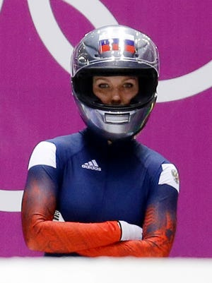 """FILE - In this Feb. 18, 2014 file photo, Nadezhda Sergeeva, of Russia, prepares for the first run during the women's two-man bobsled competition at the 2014 Winter Olympics, in Krasnaya Polyana, Russia. Sergeeva's bobsled training outfit says a lot about what life will be like for an """"Olympic Athlete from Russia."""" There is an old, anonymous black race suit with tape over several logos. Underneath, a white T-shirt with a simple message - """"I Don't Do Doping."""" As punishment for doping offenses at the 2014 Sochi Games, the International Olympic Committee has forced Russian athletes competing in Pyeongchang to do so as OARs in neutral uniforms and with no national insignia.  (AP Photo/Natacha Pisarenko, File) ORG XMIT: OLY102"""