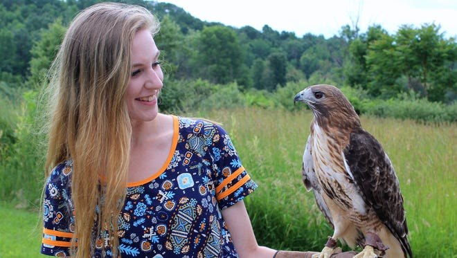 Brianna Riesbeck holds Hank, a red-tailed hawk, at Tanglewood Nature Center and Museum. Tanglewood is one of eight partners involved in a new education program.