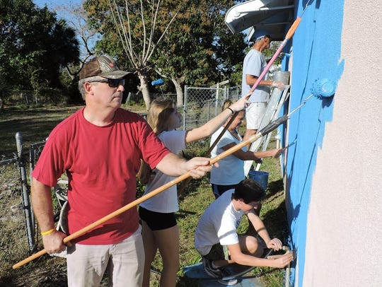 Martin County Commissioner Ed Ciampi, left, Emily Ciampi, Nick Ciampi, Liz Ciampi and Bob Connelly paint a house in East Stuart on Feb. 24, 2018.